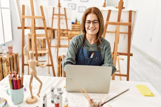 Middle age artist woman smiling happy using laptop at art studio.