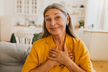 Obraz Middle-aged smiling woman feeling and showing appreciation of kindness. Elderly happy woman sitting in living room and looking at camera with with thanks. Thankfulness and gratitude concept - fototapety do salonu