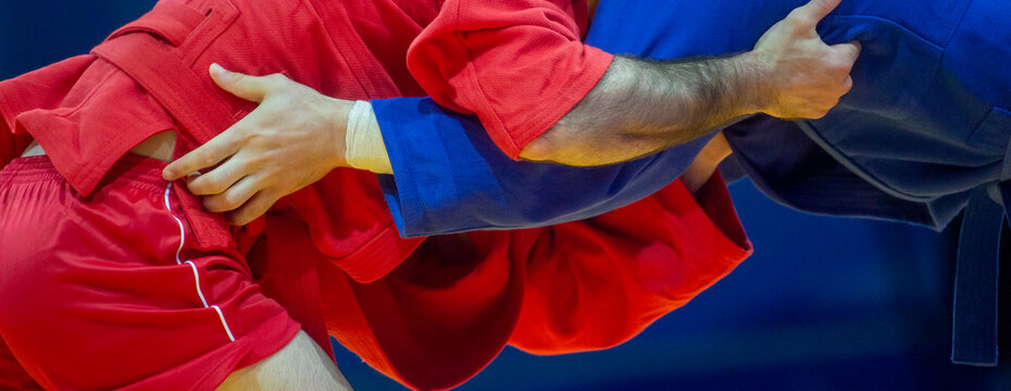 Two men in blue and red wrestling on a yellow wrestling carpet in the gym. Professional sport concept. Horizontal sport poster, greeting cards, headers, website