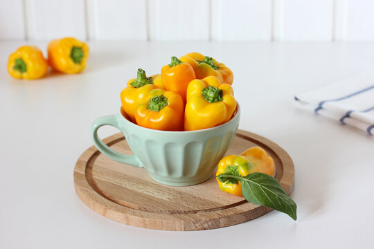 still life with yellow bell peppers on a white table.