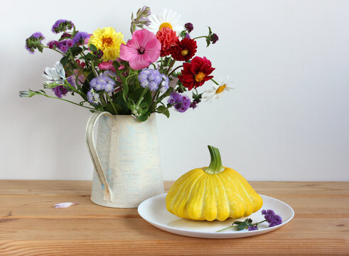 bouquet and a yellow patisson on the table.
