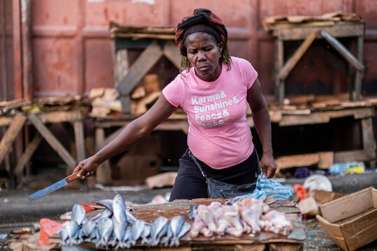 A woman drives away flies over fish and chicken for sale with a knife