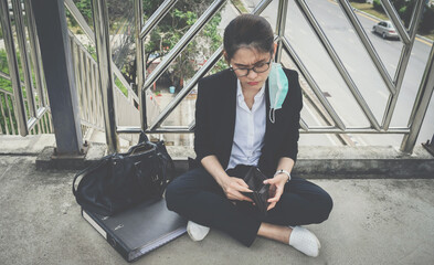 Obraz Asian unemployed businesswoman sitting on footbridge, stressed after laid off from work because impact from covid-19 pandemic outbreak. - fototapety do salonu