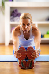Obraz Home Exercising. Woman Stretching at Home - fototapety do salonu