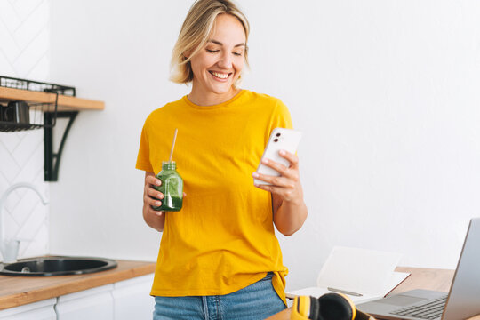 Young smiling blonde woman in yellow t-shirt with jar of green smoothies using mobile phone in hands in the kitchen at home