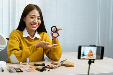 Young asian woman vlogging about cosmetics skin care items products on table with her video camera...