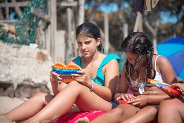 Fototapeta Group of young female teenagers playing with a colourful game on the beach. Holiday and friendship concept. obraz