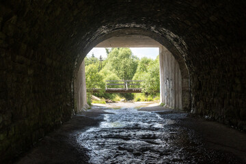 Fototapeta Tunnel with a river flowing in it and a bridge above it, which can be seen in the distance surrounded by dense greenery obraz