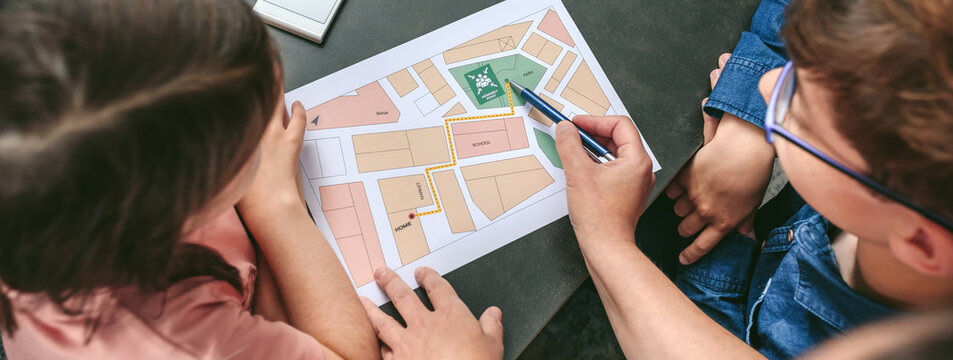 Top view of unrecognizable mother explaining to her children the assembly point map while preparing emergency backpacks