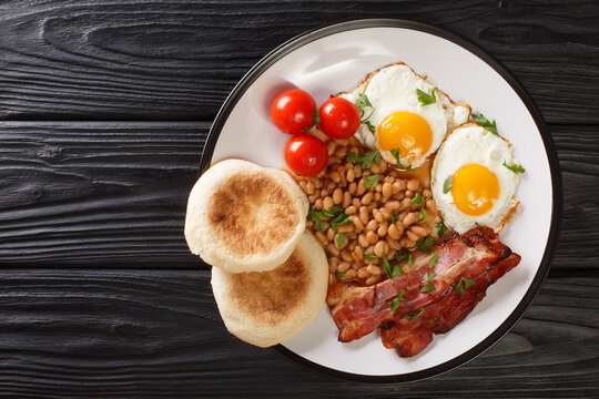 Fried eggs, beans, bacon, tomatoes and English muffins close-up in a plate on the table. horizontal top view from above
