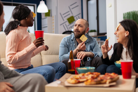 DIverse team of coworkers playing charades after work at office space. Multi ethnic friends enjoy guessing game of imiation as fun cheerful activity entertainment with food and drinks