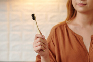 Fototapeta Young woman showing environmentally friendly wooden toothbrush obraz