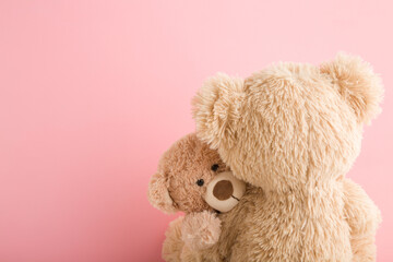 Fototapeta Brown teddy bear mother hugging her baby on light pink background. Lovely, emotional moment. Closeup. Copy space. Empty place for emotional text, cute quote or sayings. obraz