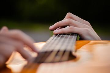 Obraz Young man playing a guitar hands close up - fototapety do salonu