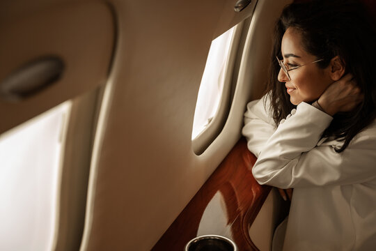 Businesswoman brunette with glasses in a white jacket flies in a charter business jet looks out the window and smiles, she is happy with his departure