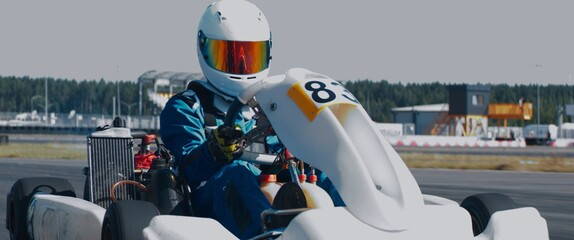 Obraz Front view of teenager professional racer driving his go kart on a race track. Shot with 2x anamorphic lens - fototapety do salonu