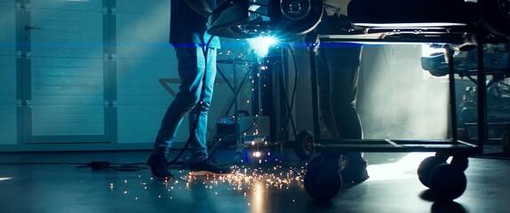 Obraz CU Sparks falling on the ground as mechanic welding a go kart car inside garage - fototapety do salonu