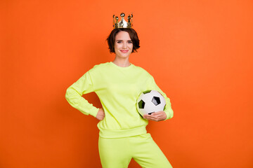 Portrait of attractive cheerful girl holding in hand ball wearing tiara isolated over vibrant...