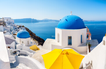 Santorini, Greece. Panoramic view of traditional houses in Santorini. Small narrow streets and rooftops of houses, churches and hotels. Oia village, Santorini Island, Greece.