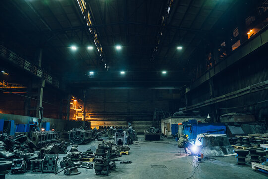 Metallurgical factory workshop interior with working welder and metal products ready for processing, heavy industry.