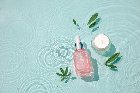 Serum glass bottle, cream jar on water with drops Concept moisturizing cosmetics