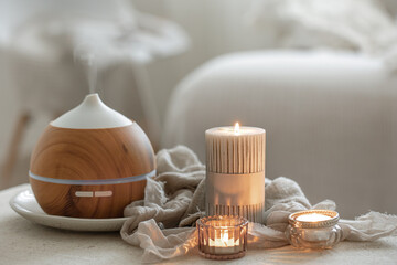 Fototapeta Cozy home composition with air humidifier and candles on blurred background. obraz