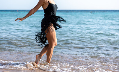 Fototapeta Attractive woman at the seaside wets her feet in the water. obraz