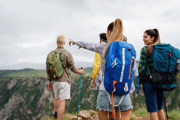 Fototapeta Group of happy friends with backpacks hiking together obraz