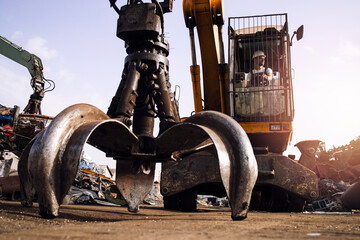 Fototapeta Man operating excavator industrial machine with claw attachment used for lifting scrap metal in junk yard. obraz
