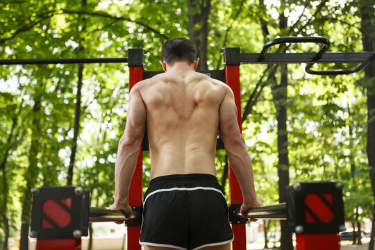 Rear view shot of an athlete with muscular back exercising on calisthenics playground