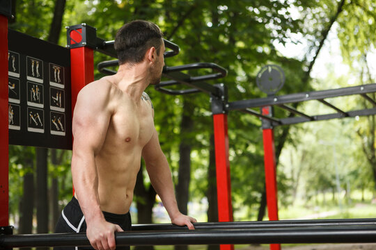 Strong muscular shirtless man working out on calisthenics workout equipment outdoors, copy space