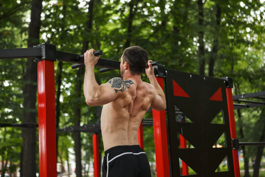 Shirtless muscular male athlete with ripped torso doing ull ups outdoors