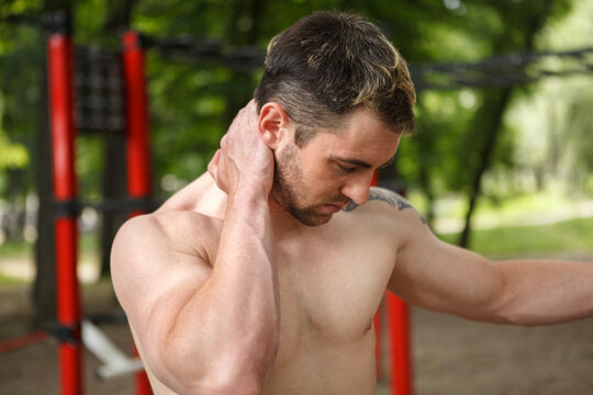 Young athletic man suffering from neck pain, massaging aching spot
