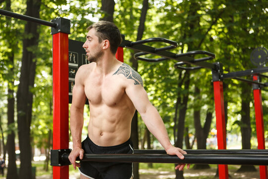 Shirtless sexy sportsman with perfect muscular body working out in the woods, copy space