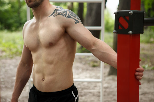 Cropped shot of a muscular shirtless athletic man resting during outdoor workout