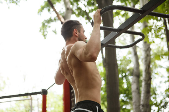 Muscular shirtless sportsman doing pull ups outdoors