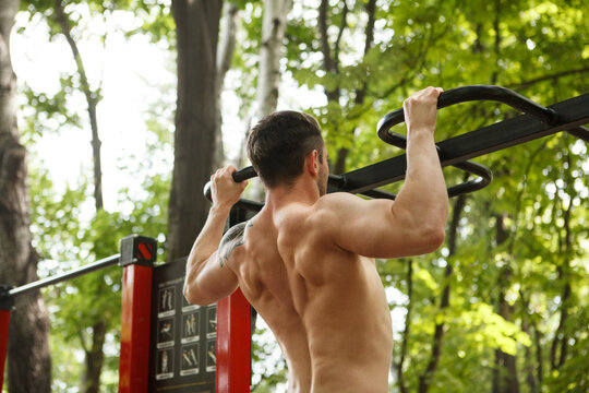 Low angle rear view shot of a muscular male athlete doing pull ups in the forest