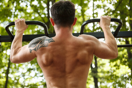 Rear view shot of a shirtless strong muscular man doing pull ups