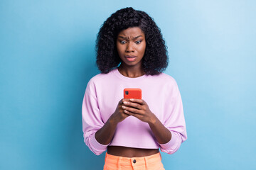 Obraz Photo portrait of unhappy woman reading fake news on smartphone isolated vibrant blue color background - fototapety do salonu