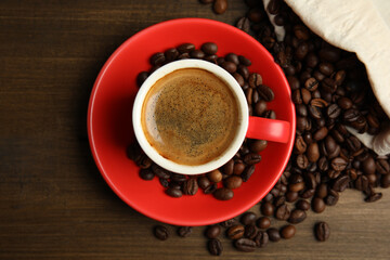 Fototapeta Cup of tasty coffee and beans on wooden table, flat lay obraz