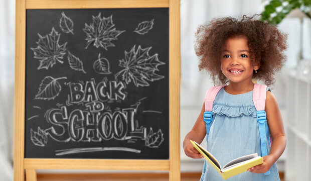 education, learning and people concept - happy little african american girl with book and backpack over chalkboard with back to school lettering on background