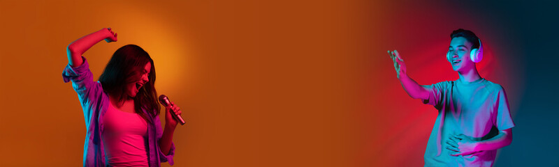 Two people, young man and woman singing and listening isolated on gradient orange background in...