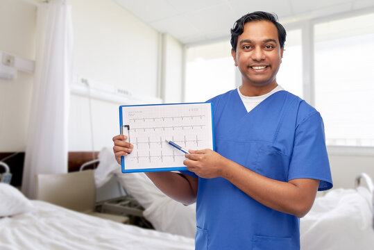 healthcare, cardiology and medicine concept - happy smiling indian doctor or male nurse in blue uniform with cardiogram on clipboard over hospital ward background