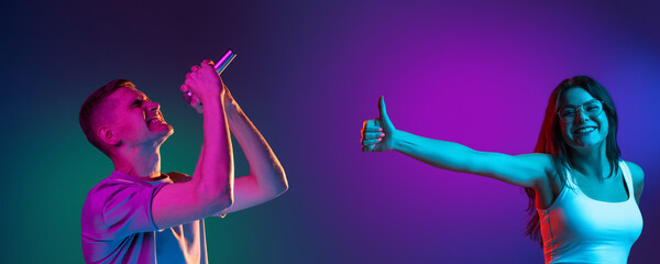 Two people, young man and woman singing and listening isolated on gradient background in neon...