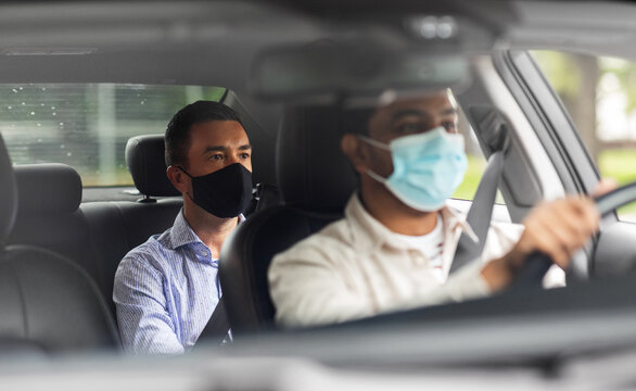 transportation, health and people concept - male passenger wearing face protective mask for protection from virus disease and indian taxi driver driving car