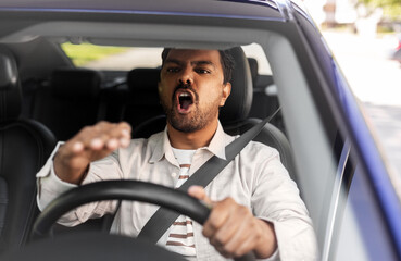 transport, vehicle and people concept - angry indian man or driver driving car