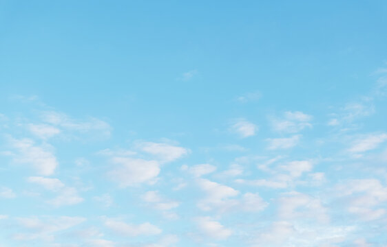 Bright blue sky with fluffy clouds and morning sunlight. Beautiful cloudscape background with copy space. Natural fresh air. Summer day season.