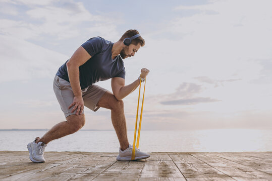 Full body young sporty strong fit sportsman man in sports clothes headphones warm up train fitness rubber bands with legs hands at sunrise over sea beach outdoor on pier seaside in summer day morning.