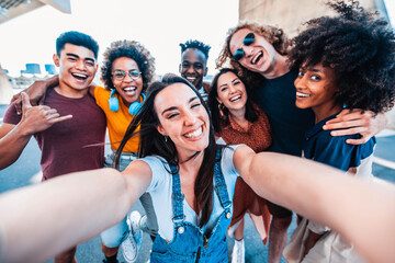 Fototapeta Multicultural happy friends having fun taking group selfie portrait on city street - Multiracial young people celebrating laughing together outdoors - Happy lifestyle concept obraz