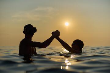 Fototapeta Młodzi przyjaciele kąpią się w morzu o zachodzie słońca. Sepia, backlight, silhouette. obraz